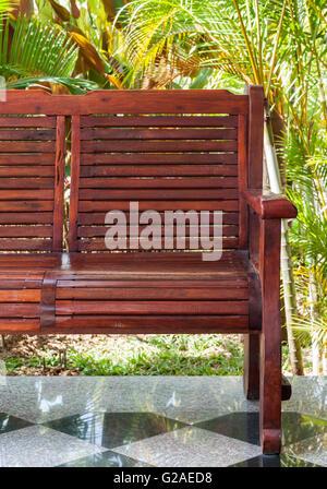Roten Holzbank auf der Terrasse in der Nähe von dem kleinen Garten des Landhaus. - Stockfoto