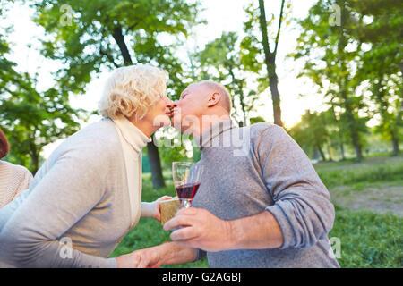 Älteres Paar küssen in einem Garten auf einer Geburtstagsfeier im Sommer - Stockfoto