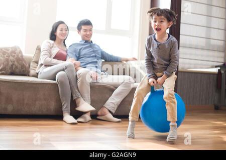 Fröhlicher Junge saß auf einem Hoppity Pferd zu Hause - Stockfoto