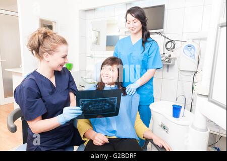 Zahnärztin und Assistent zeigt X-Ray Bild junge lächelnde Patienten in der Klinik in Zahnarztpraxis - Stockfoto