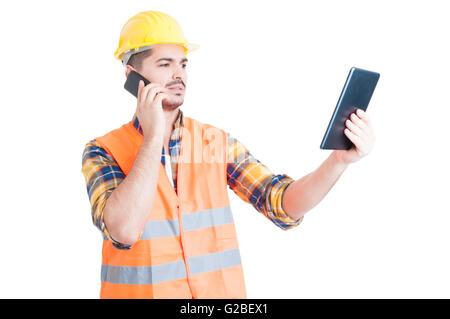 Gut aussehend Ingenieur sprechen auf Smartphone und Tablet als Multitasking oder modernes Kommunikationskonzept - Stockfoto