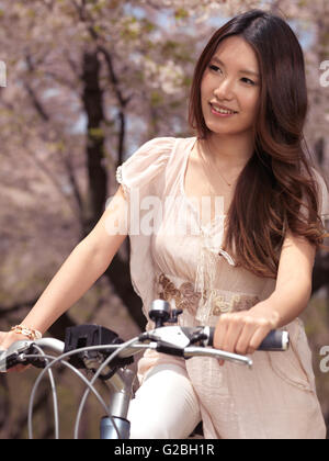 Lächelnde Frau mit dem Fahrrad vorbei an blühenden Kirschbäumen, Provinz Ontario, Kanada - Stockfoto