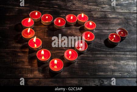 glühende kleine rote Kerzen in Herzform auf Holztisch angeordnet. Draufsicht mit Textfreiraum.