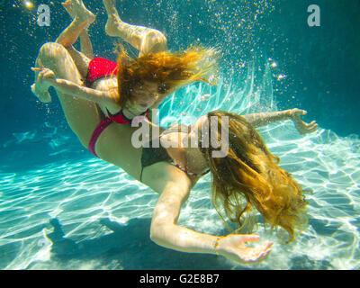 Mutter und Tochter spielen im Pool Unterwasser - Stockfoto