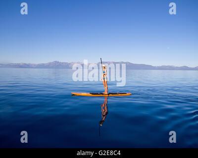 Frau stehend auf Paddleboard Paddel halten - Stockfoto