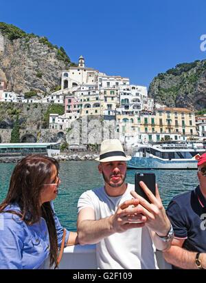 Ein Mann mit einer attraktiven jungen Frau, die ein Selbstporträt auf eine Bootsfahrt rund um die Amalfi-Küste-Italien - Stockfoto
