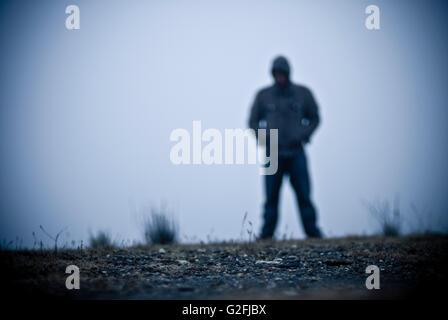 Verschwommene Kapuzengestalt im Nebel - Stockfoto