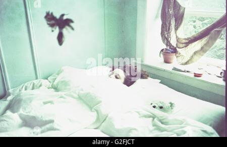 Junge Frau im Bett mit Vogel oben - Stockfoto