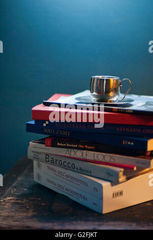 Kaffee-Tasse und Untertasse Sitting on Top of Stapel Bücher - Stockfoto