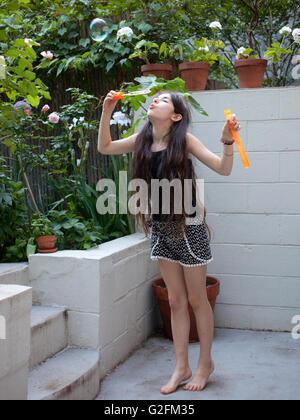 Junges Mädchen Luftblasen auf der Rückseite Veranda weht - Stockfoto