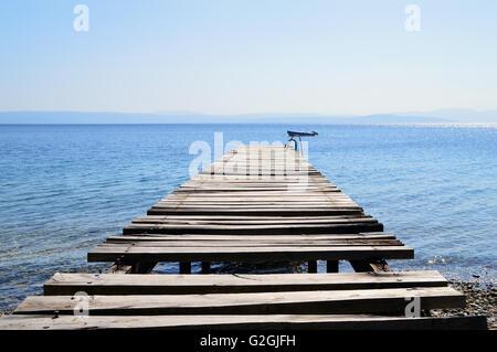 Alten gebrochen, hölzerne Pier betreten ruhige blaues Meer. Angelboot/Fischerboot in der Ferne. Ägäis, Griechenland. - Stockfoto