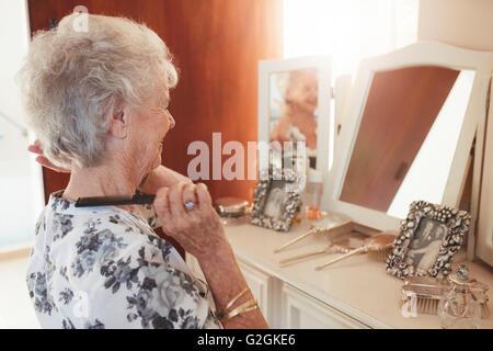 Glückliche senior Frau kämmt am Kommode im Haus. Ältere Weibchen immer vor dem Spiegel zu Hause bereit. - Stockfoto