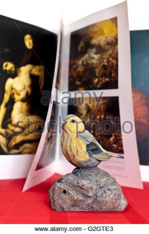 gefälschte Vogel thront auf einem Felsen platziert vor Kunstbuch auf historischen Gemälden aus dem Prado-museum - Stockfoto
