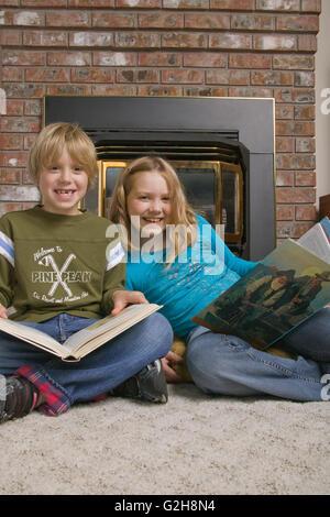 Junge und Mädchen genießen Lesung vor einem Gaskamin im Familienzimmer.  Konzepte: informelle Bildung, lernen, Faszination - Stockfoto
