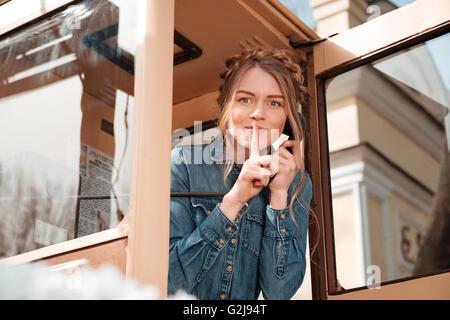 Glücklich verspielte junge Frau aus der Telefonzelle anrufen und Stille Anzeichen - Stockfoto