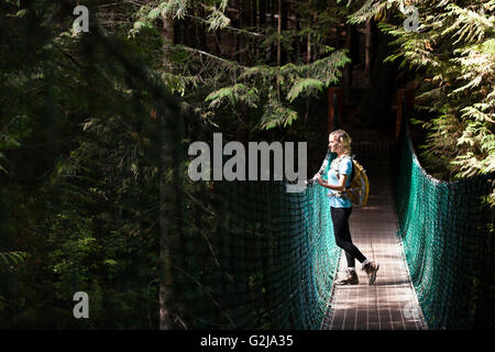 Junge Frau Wanderer auf Hängebrücke zwischen China Beach und Mystic Beach entlang Juan de Fuca Trail Vancouver Island - Stockfoto