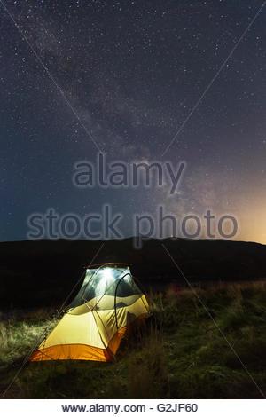 A leuchtet Zelt am Hang mit der Milchstraße und die Lichter von Kelowna über North Okanagan, Britisch-Kolumbien, - Stockfoto