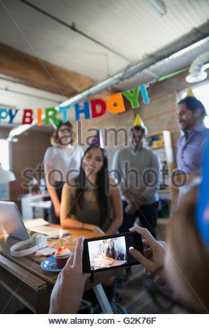 Mitarbeiter fotografieren Geschäftsfrau genießen Geburtstagsparty im Büro - Stockfoto