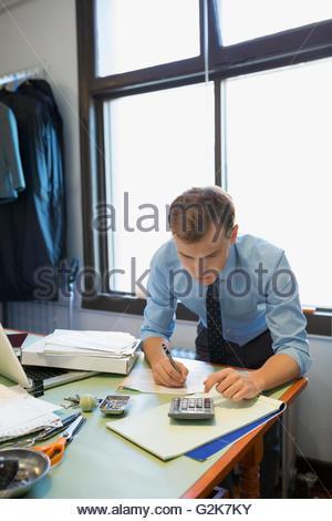 Schneiderin mit Taschenrechner und Notizen zur Werkbank - Stockfoto