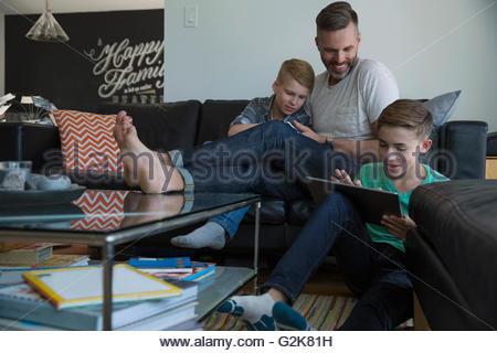 Vater und Söhne mit digitalen Tabletten im Wohnzimmer entspannen - Stockfoto