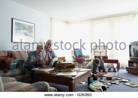 Großvater und Enkel alte Platten anhören und Erinnerungsstücke durchsehen - Stockfoto