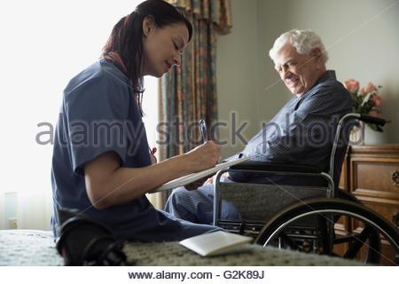 Nach Hause Pflegeperson Notizen neben älteren Mann im Rollstuhl - Stockfoto
