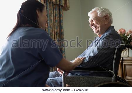 Nach Hause Bezugsperson im Gespräch mit lächelnder senior Mann im Rollstuhl - Stockfoto