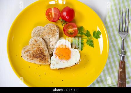 Spiegelei in Herzform, Toast, Cherry-Tomaten auf gelbe Platte - Stockfoto