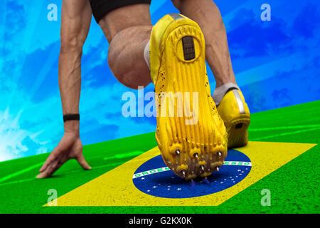 Runner ist startbereit auf Tartan Oberfläche mit brasilianischen Banner. - Stockfoto