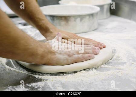 Bakers Hände Abflachung Teig - Stockfoto