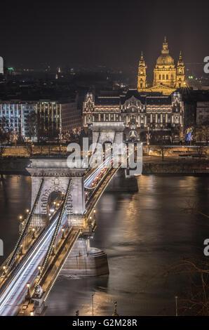 Nachtansicht der Kettenbrücke über die Donau und die St.-Stephans Basilika in Budapest, Ungarn. Vom königlichen - Stockfoto