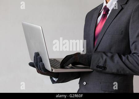 Geschäftsmann, tragen von Handschuhen und Computer - Hacker, Diebstahl, Betrug, Cyber-Kriminalität-Konzept - Stockfoto