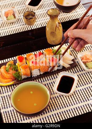 Nahaufnahme der Hand eines Mannes mit Stäbchen essen Sushi in einem japanischen restaurant - Stockfoto