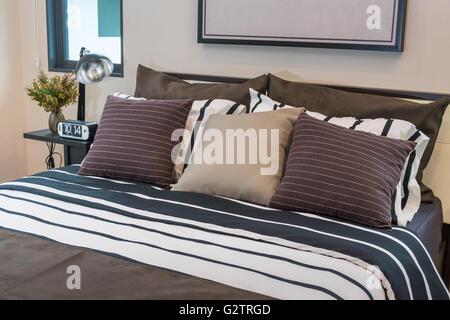 Moderne Schlafzimmer mit Lampe, Uhr und Kissen - Stockfoto