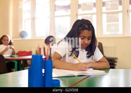 Weibliche Schüler arbeiten am Schreibtisch im Klassenzimmer der Grundschule - Stockfoto