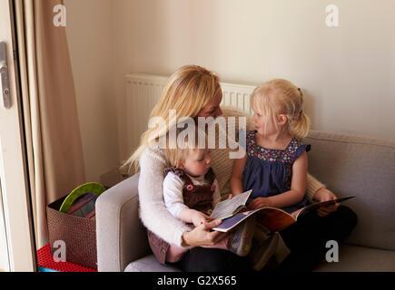 Mutter sitzt auf dem Sofa lesen Geschichte mit Töchter - Stockfoto