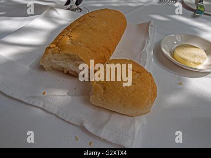 Knuspriges Weißbrot mit einer Schüssel mit Butter auf einer weißen Tischdecke - Stockfoto