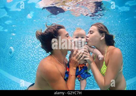 Glückliche Familie - Vater, Mutter mit Baby Schwimmen Schwimmen und Tauchen unter Wasser mit Spaß im Schwimmbad. - Stockfoto
