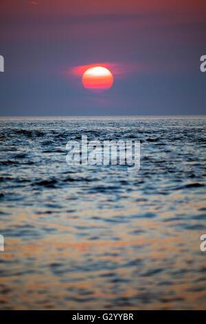 Ein Sommer Sonne über der Irischen See in Penmon Punkt auf der Insel Anglesey, Wales, Großbritannien - Stockfoto