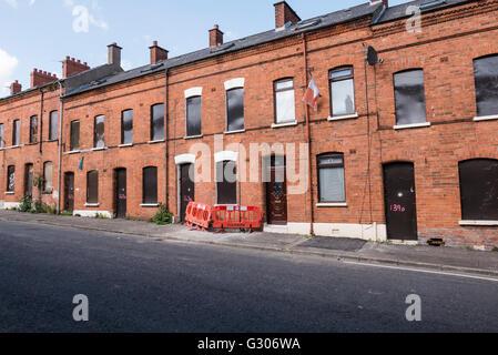 Eine lange Reihe von verlassenen Häusern in einer Straße mit Stahlplatten mit Brettern vernagelt. - Stockfoto