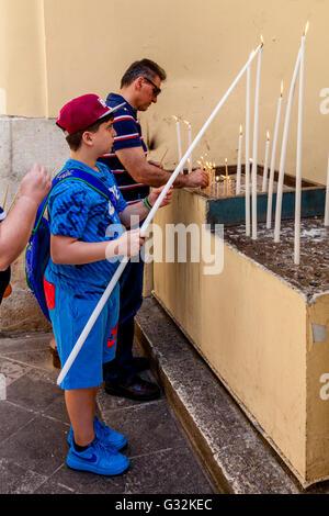 Ein kleiner Junge zündet eine Kerze außerhalb St. Spyridon Kirche, Altstadt von Korfu, Korfu, Griechenland - Stockfoto