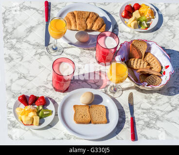 Set Tisch mit verschiedenen Speisen und Getränke zum Frühstück an sonnigen Tag in der Sommersaison - Stockfoto