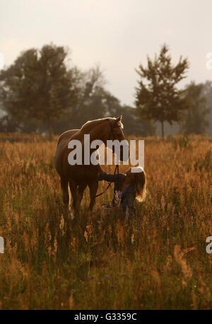 Brieselang, Deutschland, Mädchen kauert auf einer Wiese auf ihr Pferd und betrachtet ihn liebevoll - Stockfoto