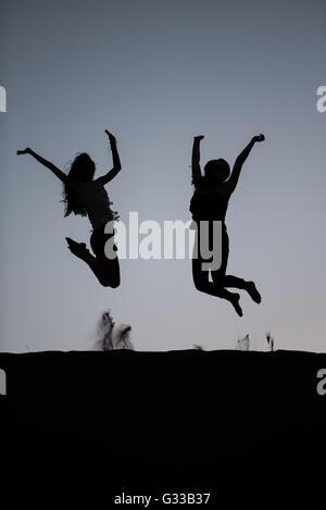 Zwei Jugendliche springen vor Freude auf einer Sanddüne - Stockfoto
