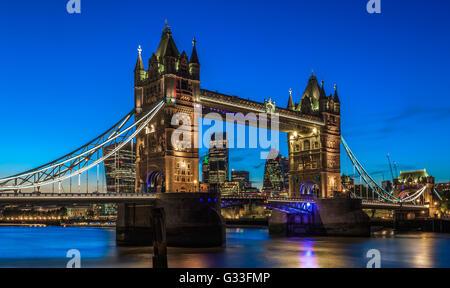 Beleuchtete Tower Bridge in London nach Sonnenuntergang mit Londons Finanzviertel im Hintergrund