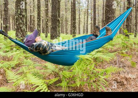 Reife Frauen Wanderer zum Entspannen in der Hängematte im Pinienwald. Einsatzmöglichkeiten: Reifen Backpacker / - Stockfoto