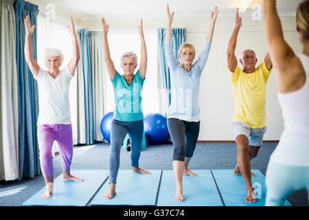 Kursleiter Yoga mit Senioren durchführen - Stockfoto