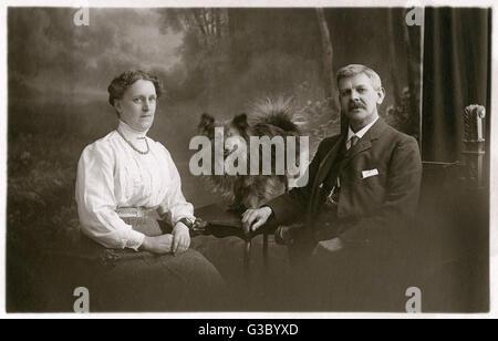 Ein Ehepaar mittleren Alters mit ihrem Hund in einem Studio-Foto.      Datum: ca. 1920er Jahre - Stockfoto