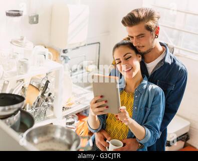 Liebevolle junge Paar mit digital-Tablette in Appartement Küche - Stockfoto