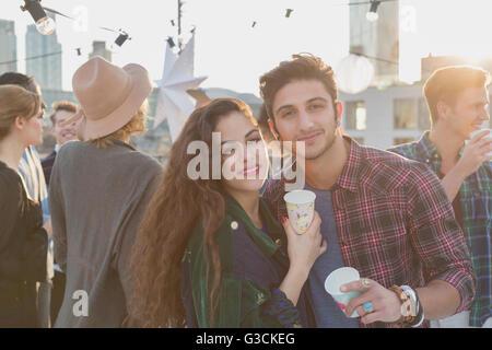 Porträt, Lächeln junges Paar trinken auf Party auf dem Dach - Stockfoto